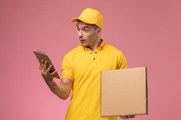Männlicher kurier der vorderansicht in der gelben uniform, die notizblock zusammen mit nahrungsmittellieferbox auf dem rosa hintergrund hält