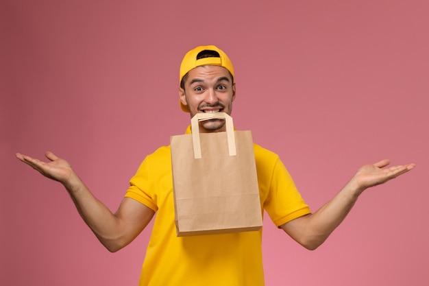 Männlicher kurier der vorderansicht in der gelben uniform, die papierliefernahrungsmittelpaket mit seinem mund auf rosa hintergrund hält.