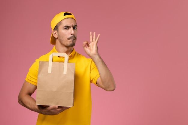 Männlicher kurier der vorderansicht in der gelben uniform, die papierlieferungsnahrungsmittelpaket auf dem rosa hintergrund hält.