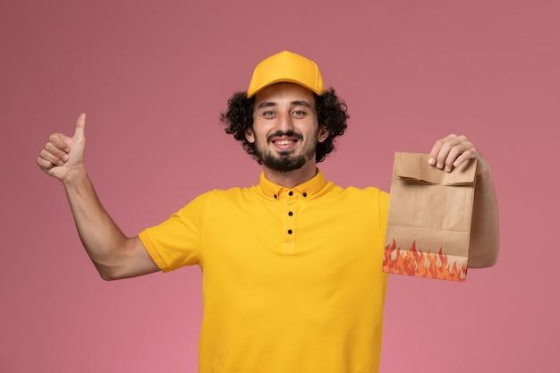 Männlicher kurier der vorderansicht in der gelben uniform, die papiernahrungsmittelpaket auf hellrosa wand hält