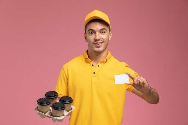 Männlicher kurier der vorderansicht in der gelben uniform, die plastikkarte und lieferkaffeetassen auf dem rosa hintergrund hält