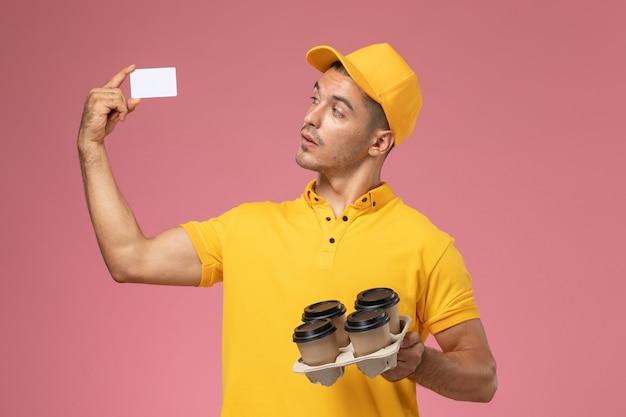 Männlicher kurier der vorderansicht in der gelben uniform, die plastikkarte und lieferkaffeetassen auf hellrosa hintergrund hält