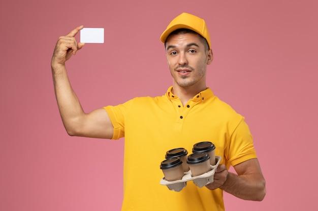 Männlicher kurier der vorderansicht in der gelben uniform, die plastikkarte und lieferkaffeetassen auf rosa schreibtisch hält