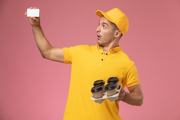 Männlicher kurier der vorderansicht in der gelben uniform, die plastikkarte und lieferkaffeetassen mit überraschtem ausdruck auf rosa schreibtisch hält