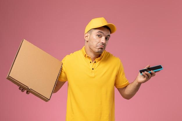 Männlicher kurier der vorderansicht in der gelben uniform, die sein telefon und essenslieferbox auf rosa schreibtisch hält