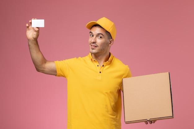Männlicher kurier der vorderansicht in der gelben uniform, die weiße karte und essenslieferbox auf dem rosa schreibtisch hält