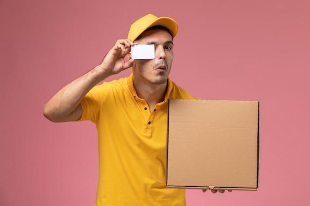 Männlicher kurier der vorderansicht in der gelben uniform, die weiße karte und nahrungsmittelbox auf dem rosa hält