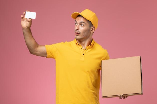 Männlicher kurier der vorderansicht in der gelben uniform, die weiße karte und nahrungsmittellieferbox auf rosa hält