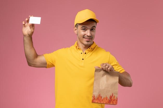 Männlicher kurier der vorderansicht in der gelben uniform lächelnd, die weiße karte und lebensmittelpaket auf rosa schreibtisch hält