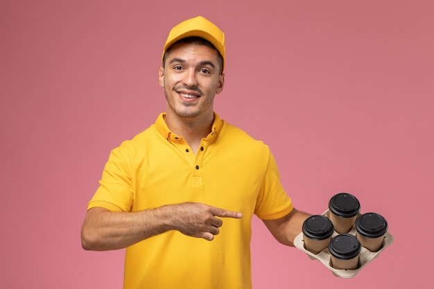 Männlicher kurier der vorderansicht in der gelben uniform lächelnd und hält lieferkaffeetassen auf dem rosa