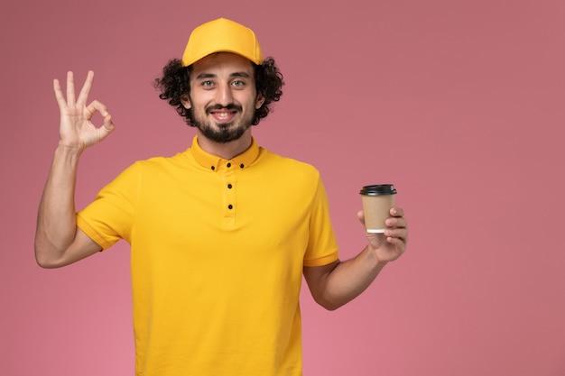 Männlicher kurier der vorderansicht in der gelben uniform und im umhang, der die kaffeetasse der lieferung an der rosa wand hält