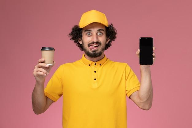 Männlicher kurier der vorderansicht in der gelben uniform und im umhang, der die kaffeetasse und das telefon der lieferung an der rosa wand hält