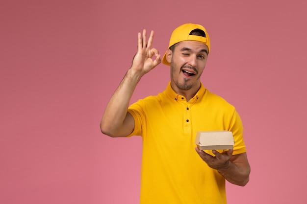 Männlicher kurier der vorderansicht in der gelben uniform und im umhang, der kleines liefernahrungsmittelpaket hält, das auf rosa hintergrund zwinkert.