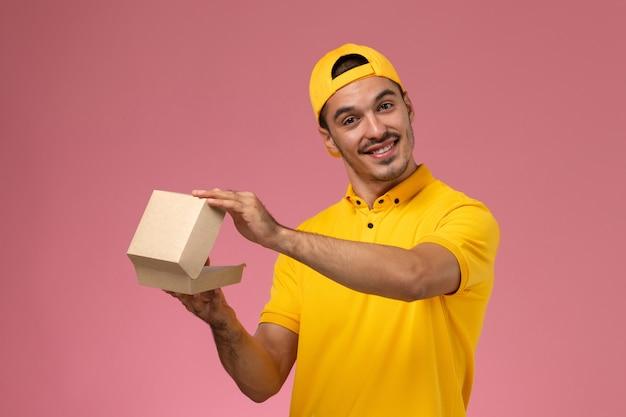 Männlicher kurier der vorderansicht in der gelben uniform und im umhang, der kleines liefernahrungsmittelpaket hält, das auf rosa schreibtisch lächelt.