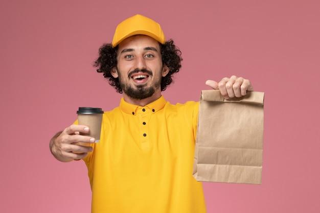 Männlicher kurier der vorderansicht in der gelben uniform und im umhang, der lieferung kaffeetasse-lebensmittelpaket an der rosa wand hält