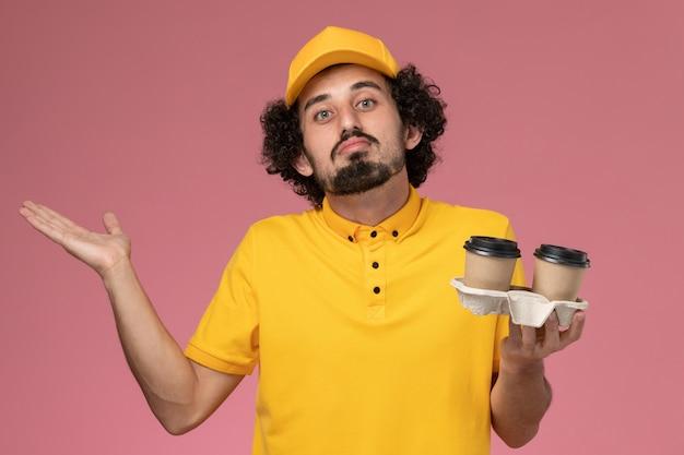 Männlicher kurier der vorderansicht in der gelben uniform und im umhang, die braune kaffeetassen der lieferung auf rosa wand halten