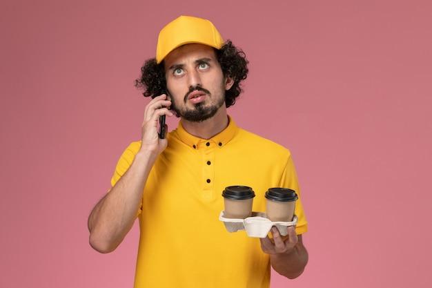Männlicher kurier der vorderansicht in der gelben uniform und im umhang, die braune kaffeetassen der lieferung halten, die am telefon auf rosa wand sprechen