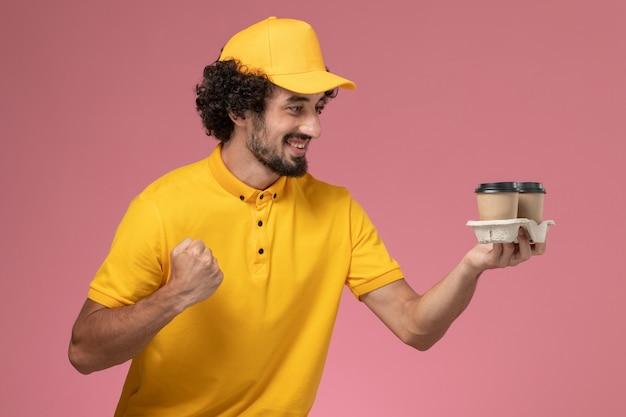 Männlicher kurier der vorderansicht in der gelben uniform und im umhang, die braune kaffeetassen der lieferung halten, die auf rosa wand jubeln