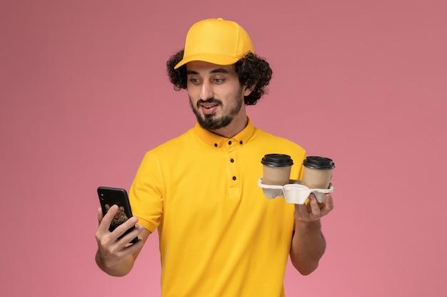 Männlicher kurier der vorderansicht in der gelben uniform und im umhang, die braune kaffeetassen der lieferung halten und ein telefon auf rosa wand verwenden