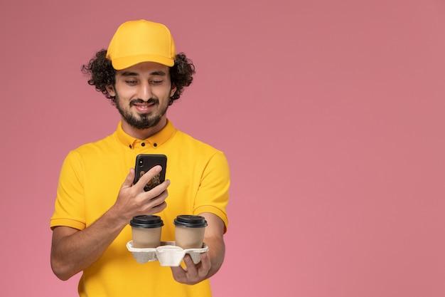 Männlicher kurier der vorderansicht in der gelben uniform und im umhang, die braune kaffeetassen der lieferung halten und foto von ihnen auf rosa wand machen