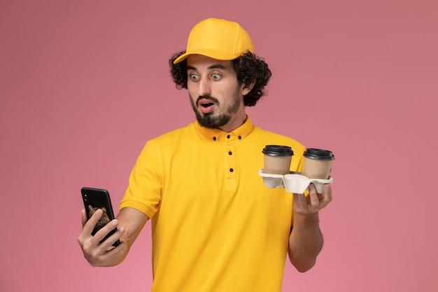 Männlicher kurier der vorderansicht in der gelben uniform und im umhang, die braune kaffeetassen und telefon der lieferung an der rosa wand halten