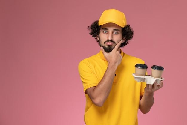 Männlicher kurier der vorderansicht in der gelben uniform und im umhang, die braune lieferkaffeetassen halten, die an rosa wand denken