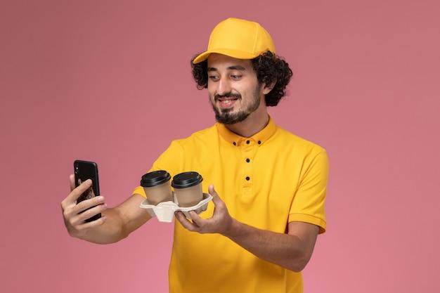 Männlicher kurier der vorderansicht in der gelben uniform und im umhang, die braune lieferkaffeetassen halten foto auf rosa wand machen