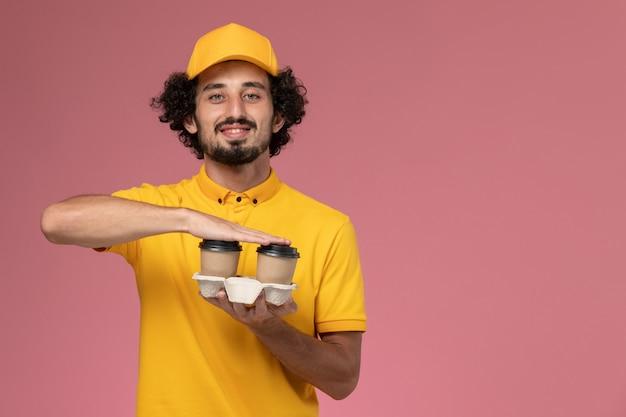 Männlicher kurier der vorderansicht in der gelben uniform und im umhang, die braune lieferkaffeetassen mit einem lächeln auf der rosa wand halten