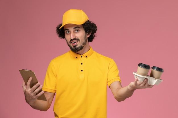 Männlicher kurier der vorderansicht in der gelben uniform und im umhang, die braune lieferkaffeetassen und notizblock an der rosa wand halten