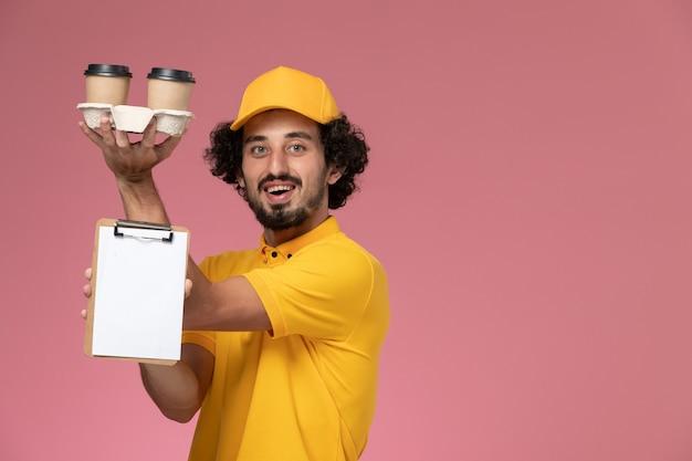 Männlicher kurier der vorderansicht in der gelben uniform und im umhang, die braune lieferkaffeetassen und notizblock auf hellrosa wand halten