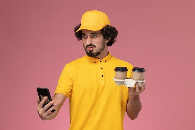Männlicher kurier der vorderansicht in der gelben uniform und im umhang, die braune lieferkaffeetassen und sein telefon auf rosa wand halten