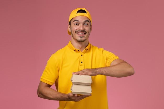 Männlicher kurier der vorderansicht in der gelben uniform und im umhang, die kleine liefernahrungsmittelpakete auf dem hellrosa hintergrund halten.