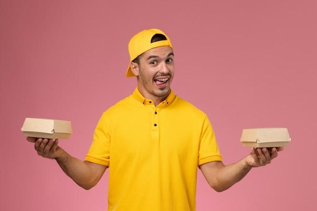 Männlicher kurier der vorderansicht in der gelben uniform und im umhang, die kleine liefernahrungsmittelpakete auf dem rosa hintergrund halten.