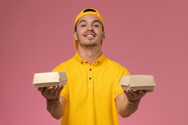 Männlicher kurier der vorderansicht in der gelben uniform und im umhang, die kleine liefernahrungsmittelpakete auf rosa schreibtisch halten.