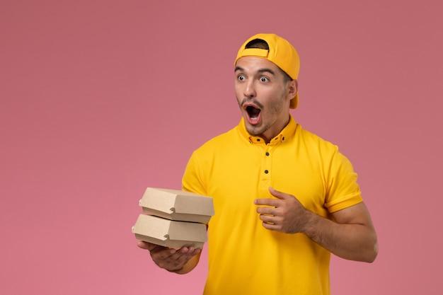 Männlicher kurier der vorderansicht in der gelben uniform und im umhang, die kleine liefernahrungsmittelpakete mit überraschtem ausdruck auf dem hellrosa hintergrund halten.