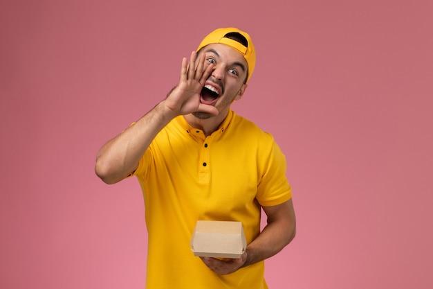 Männlicher kurier der vorderansicht in der gelben uniform und im umhang, die kleines liefernahrungsmittelpaket auf dem rosa hintergrund halten.