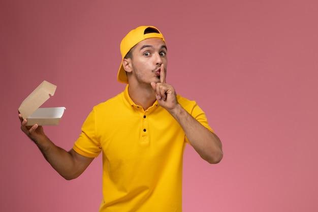 Männlicher kurier der vorderansicht in der gelben uniform und im umhang, die kleines liefernahrungsmittelpaket auf hellrosa hintergrund halten.
