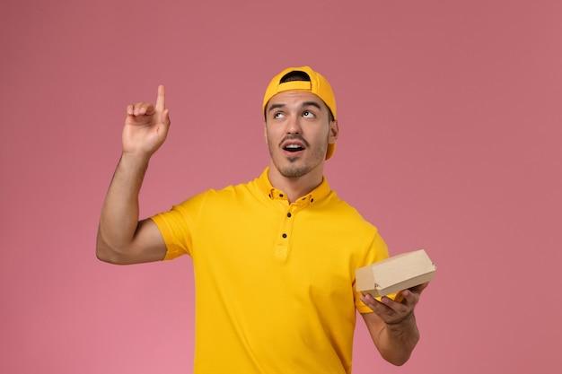 Männlicher kurier der vorderansicht in der gelben uniform und im umhang, die kleines liefernahrungsmittelpaket auf rosa schreibtisch halten.