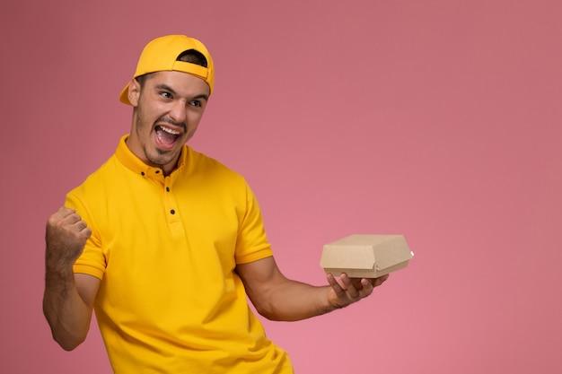 Männlicher kurier der vorderansicht in der gelben uniform und im umhang, die kleines liefernahrungsmittelpaket halten, das auf rosa hintergrund jubelt.