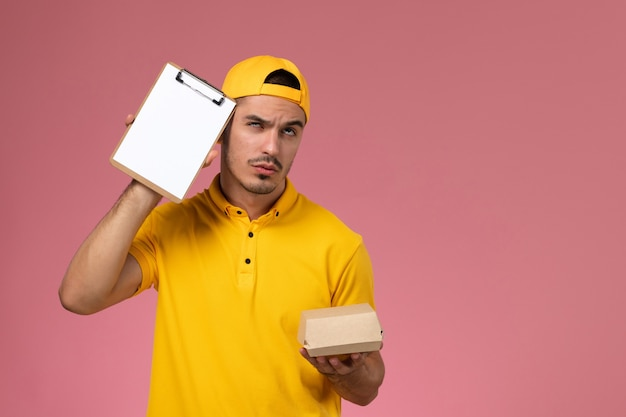 Männlicher kurier der vorderansicht in der gelben uniform und im umhang, die kleines liefernahrungsmittelpaket und notizblock mit denkendem ausdruck auf rosa schreibtisch halten.