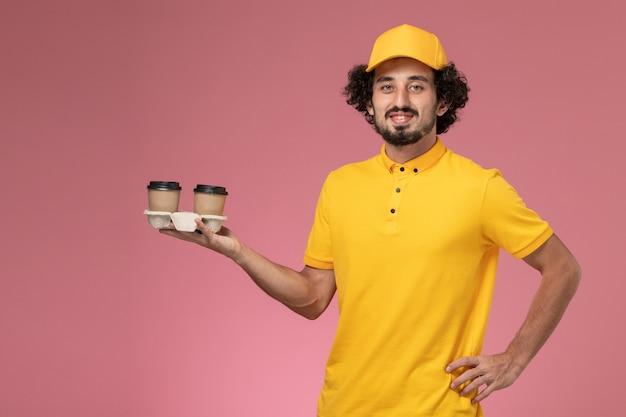 Männlicher kurier der vorderansicht in der gelben uniform und im umhang, die lieferkaffeetassen auf rosa wand halten