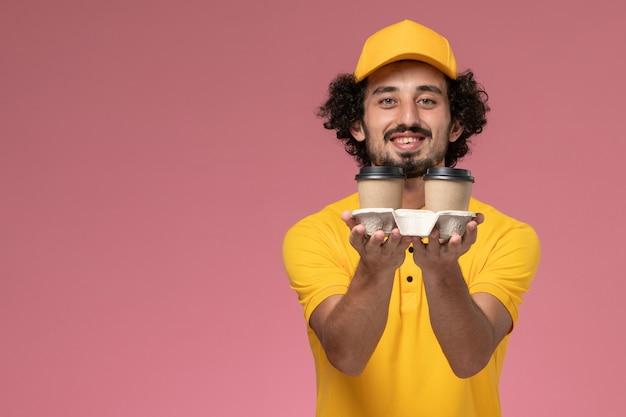 Männlicher kurier der vorderansicht in der gelben uniform und im umhang, die lieferkaffeetassen mit lächeln an der rosa wand halten