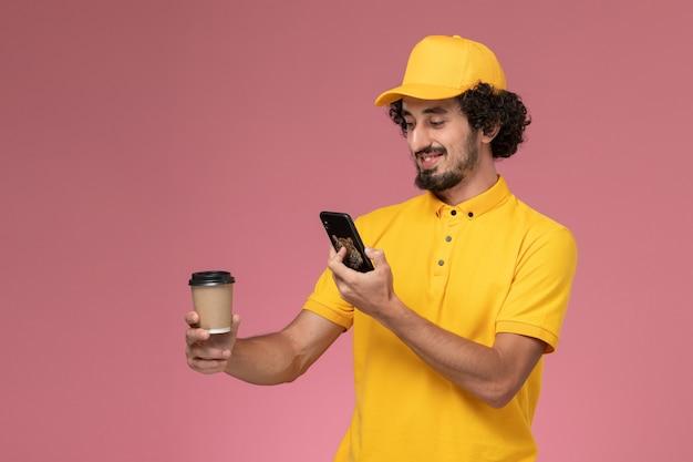 Männlicher kurier der vorderansicht in der gelben uniform und im umhang, die lieferung kaffeetasse halten foto auf der rosa wand halten