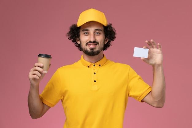 Männlicher kurier der vorderansicht in der gelben uniform und im umhang, die lieferung kaffeetasse und karte auf rosa wand halten