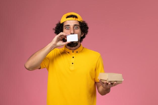 Männlicher kurier der vorderansicht in der gelben uniform und im umhang mit karte und kleinem liefernahrungsmittelpaket auf seinen händen auf dem hellrosa hintergrund.