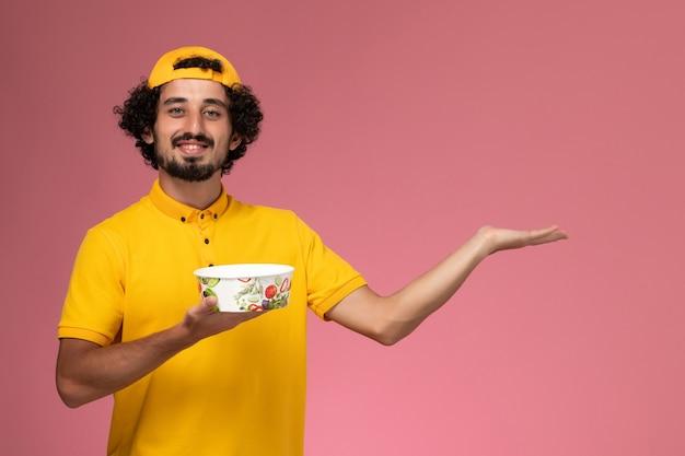 Männlicher kurier der vorderansicht in der gelben uniform und im umhang mit runder lieferschale auf seinen händen auf dem hellrosa hintergrund.