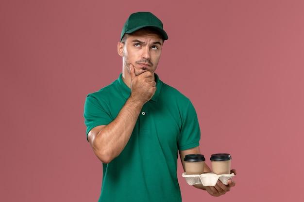 Männlicher kurier der vorderansicht in der grünen uniform, die braune kaffeetassen auf rosa hintergrund denkt und hält
