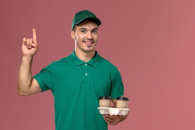 Männlicher kurier der vorderansicht in der grünen uniform, die braune kaffeetassen der lieferung auf hellrosa boden hält
