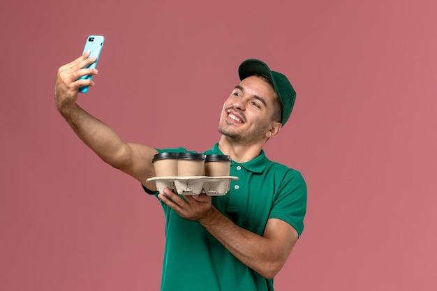 Männlicher kurier der vorderansicht in der grünen uniform, die braune kaffeetassen hält, die foto mit ihnen auf rosa schreibtisch machen
