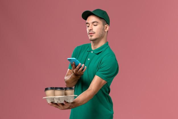 Männlicher kurier der vorderansicht in der grünen uniform, die braune kaffeetassen hält, die foto von ihnen auf rosa hintergrund machen